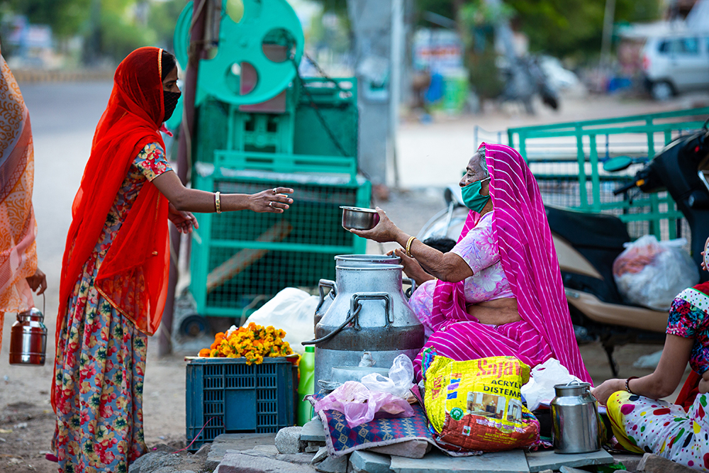Roadside kirana vendor and customer wearing face masks in Rajasthan.