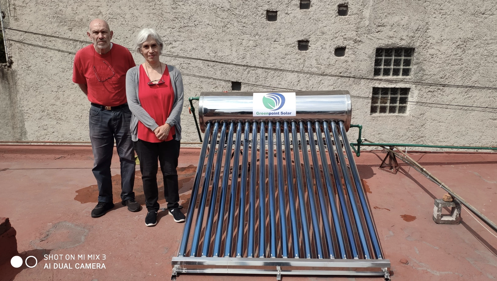 Graviti's customers stand next to their newly purchased solar water heater